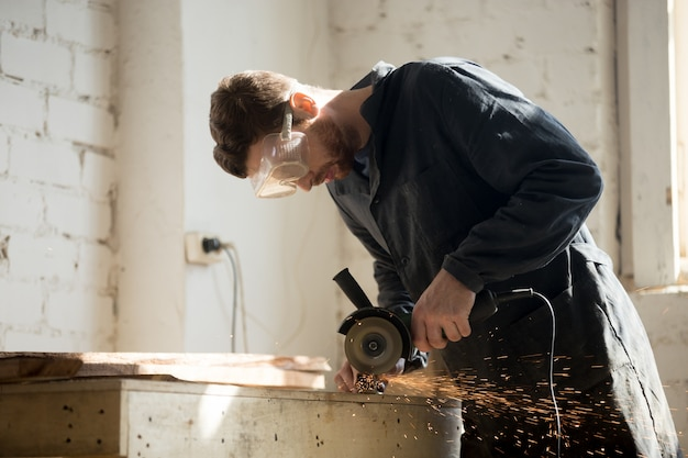 Zijaanzicht van de werknemer met behulp van hoek grinder voor metalen snijden