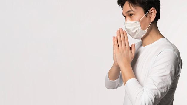 Zijaanzicht van de zieke man met medische masker bidden