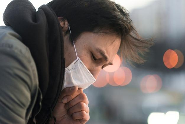 Zijaanzicht van de zieke man met medische masker hoesten