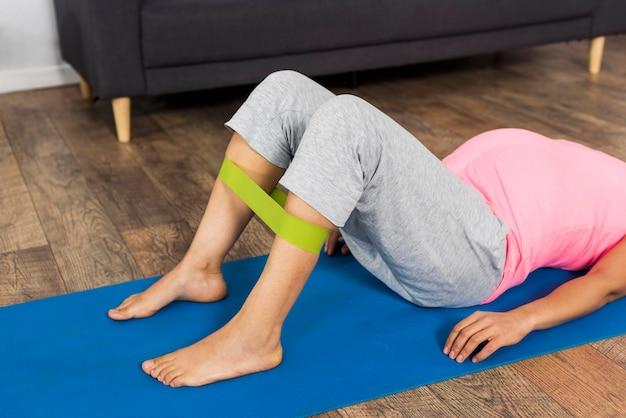 Zijaanzicht van de zwangere vrouw die thuis met elastische band op mat oefent