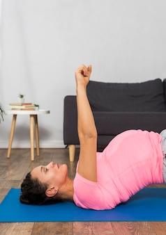 Zijaanzicht van de zwangere vrouw die thuis op mat uitoefent