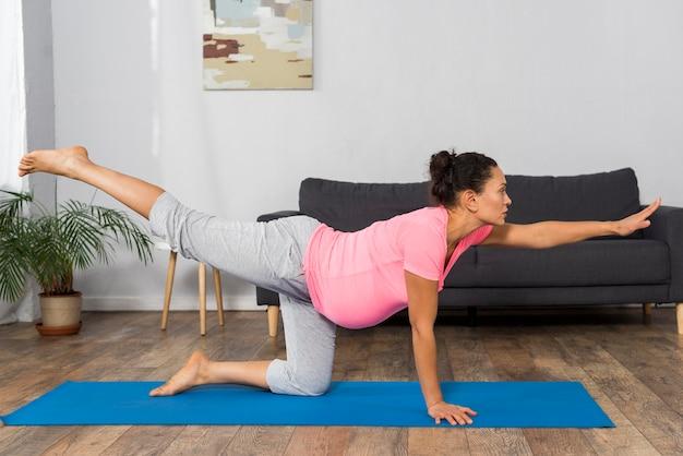 Zijaanzicht van de zwangere vrouw die thuis yoga doet