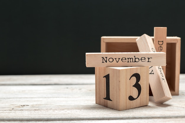 Zijaanzicht van delen van houten kalender op donker houten tafelblad