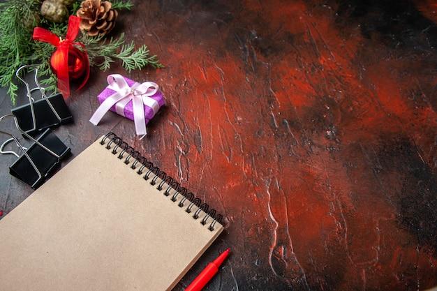 Zijaanzicht van dennentakken decoratie accessoires en cadeau naast notebook met pen op donkere achtergrond