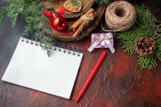 Zijaanzicht van dennentakken en gesloten spiraalvormig notitieboekje met pen kaneel limoenen bal van touw op donkere tafel