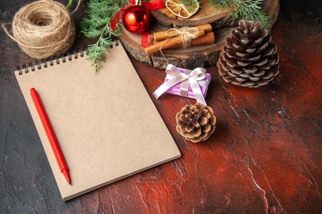 Zijaanzicht van dennentakken en gesloten spiraalvormig notitieboekje met pen, kaneellimoenen, coniferenkegel en bal van touw op donkere achtergrond
