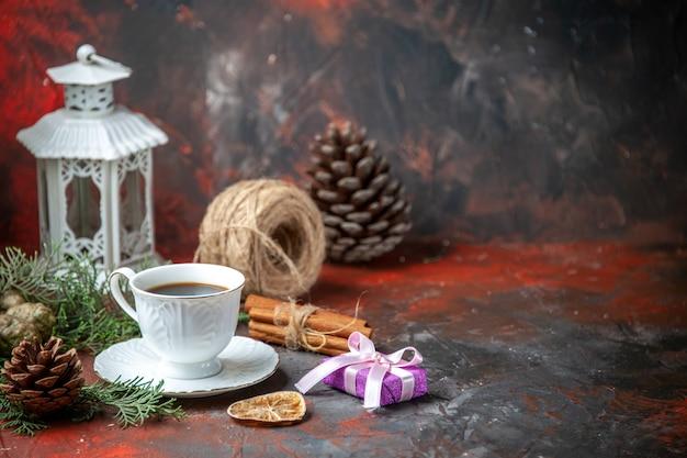 Zijaanzicht van dennentakken kaneel limoenen conifer kegel een bal van touw een kopje zwarte thee op rode achtergrond