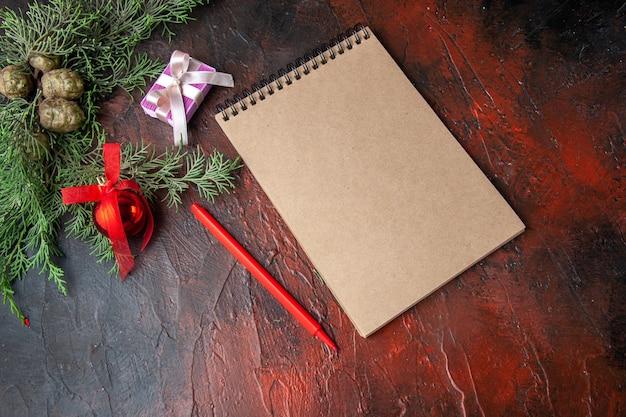 Zijaanzicht van dennentakken met decoratieaccessoires en cadeau naast notitieboekje op donkere achtergrond