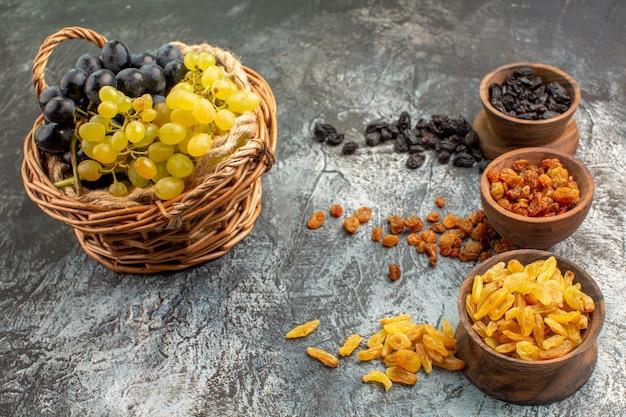 Zijaanzicht van dichtbij druivenkommen met gedroogde vruchten de smakelijke druiven in de mand