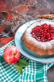 Zijaanzicht van dichtbij een cake een cake met rode aalbessen appel op het tafelkleed vorken kaneel