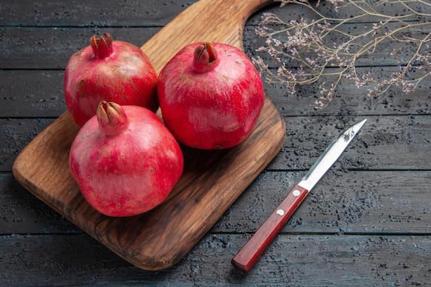 Zijaanzicht van dichtbij granaatappels aan boord van rijpe granaatappels op snijplank naast mes en boomtakken
