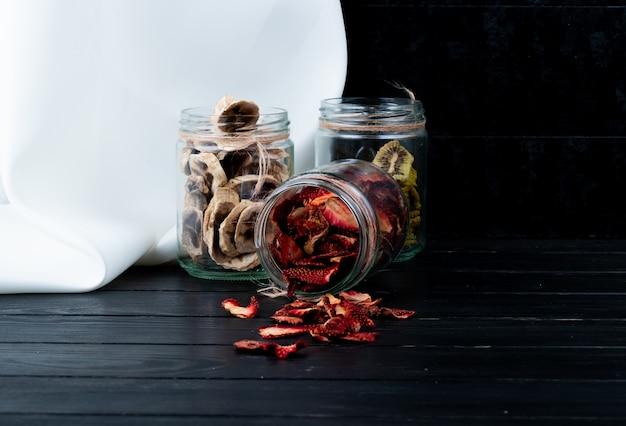 Zijaanzicht van diverse gedroogd fruitplakken in de aardbeibanaan en kiwi van glaskruiken op zwarte achtergrond met exemplaarruimte