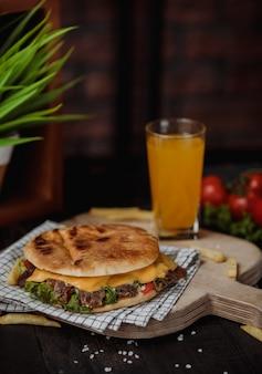 Zijaanzicht van doner kebab in pitabroodje op een houten raad