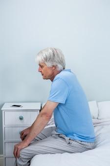 Zijaanzicht van doordachte senior man zittend op bed