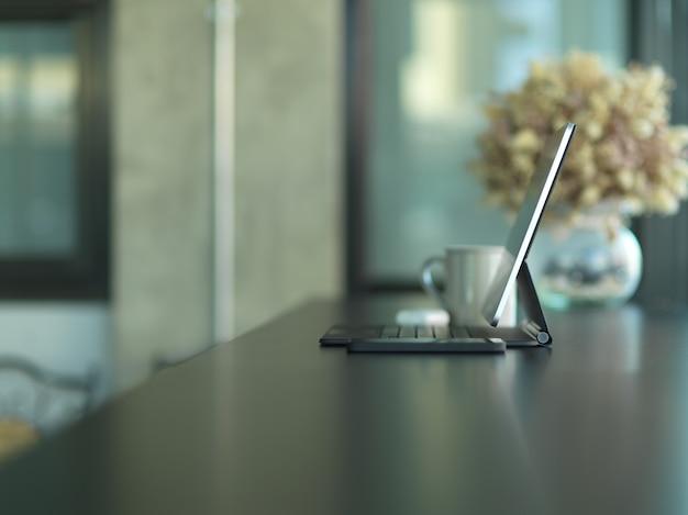 Zijaanzicht van draagbare werkruimte met tablet, beker en bloemenvaas op zwarte tafel