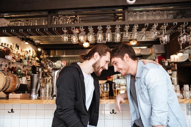 Zijaanzicht van dronken vrienden op bar