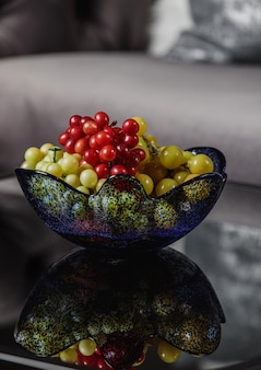 Zijaanzicht van druiven in een glazen vaas op tafel