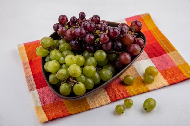 Zijaanzicht van druiven in kom op geruite doek en op witte achtergrond