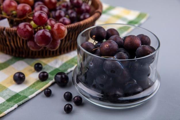 Zijaanzicht van druivenbessen in glazen kom met mand met druivenmost op geruite doek op grijze achtergrond