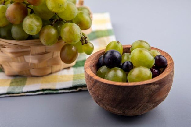 Zijaanzicht van druivenbessen in kom met mand met druivenmost op geruite doek en grijze achtergrond