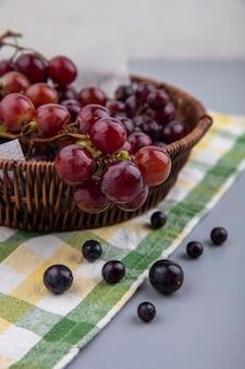 Zijaanzicht van druivenbessen met mand met druiven op geruite doek op grijze achtergrond