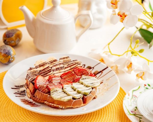 Zijaanzicht van dunne pannenkoek met aardbeien, bananen en kiwi bedekt met chocoladesaus op witte plaat