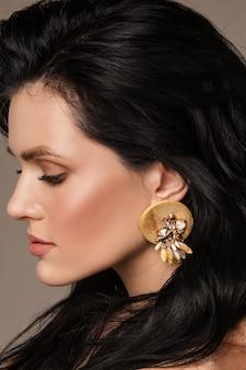 Zijaanzicht van een aantrekkelijk kaukasisch model met donker haar dat naar beneden kijkt en een modieuze handgemaakte oorbel van leer en stenen draagt.