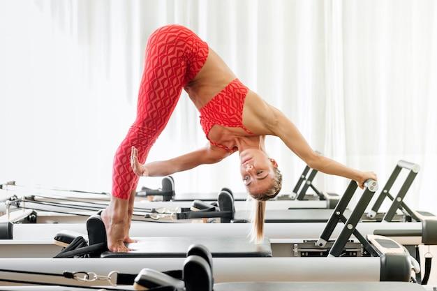 Zijaanzicht van een aantrekkelijke fit atletische jonge vrouw die een pilates dolfijn yoga pose variatie doet met behulp van een hervormer in een sportschool in een gezonde actieve levensstijl concept
