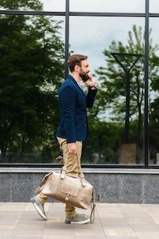 Zijaanzicht van een aantrekkelijke glimlachende jonge, bebaarde man met een jas die buiten op straat loopt, een tas draagt, praat op een mobiele telefoon