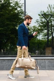 Zijaanzicht van een aantrekkelijke jonge, bebaarde man met een jas die buiten op straat loopt, een tas draagt, een mobiele telefoon vasthoudt
