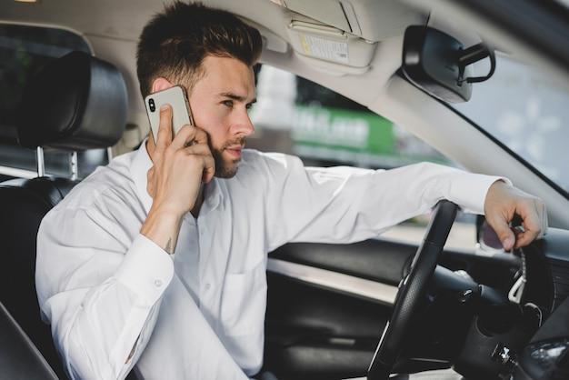 Zijaanzicht van een aantrekkelijke jonge man zit in de auto praten op smartphone