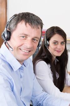Zijaanzicht van een aantrekkelijke jongeman in een callcenter