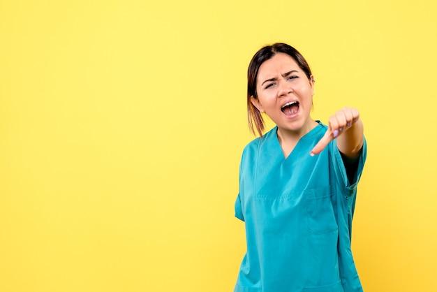 Zijaanzicht van een arts in het medische uniform heeft het over het gedrag van de patiënten