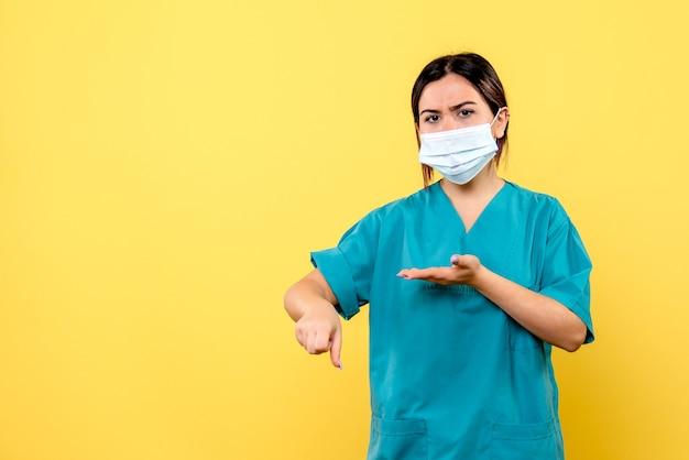 Zijaanzicht van een arts in masker praat patiënten met de covid