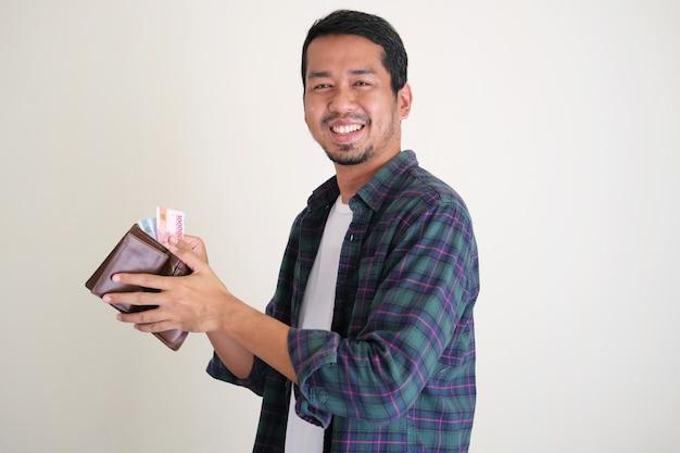 Zijaanzicht van een aziatische man die blij lacht als hij papiergeld uit zijn portemonnee haalt