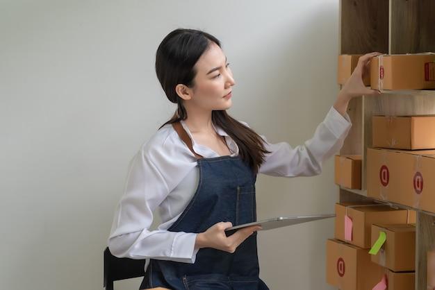 Zijaanzicht van een aziatische online bedrijfseigenaar die een tablet vasthoudt om de pakketdoos te controleren voordat hij thuis aan klanten levert.