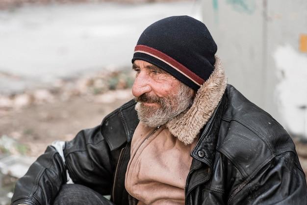 Zijaanzicht van een bebaarde dakloze man buitenshuis