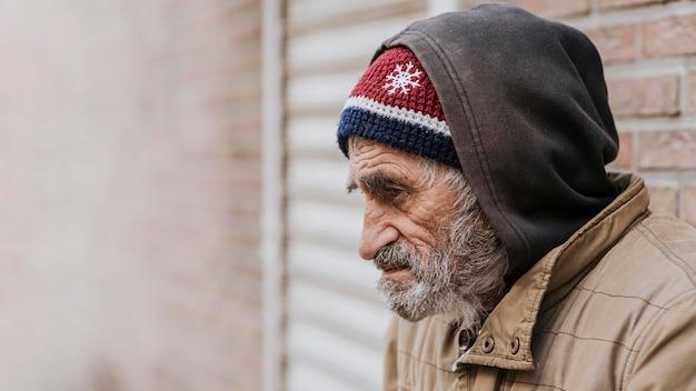 Zijaanzicht van een bebaarde dakloze man met kopie ruimte