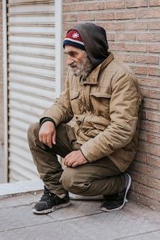 Zijaanzicht van een bebaarde dakloze man voor bakstenen muur