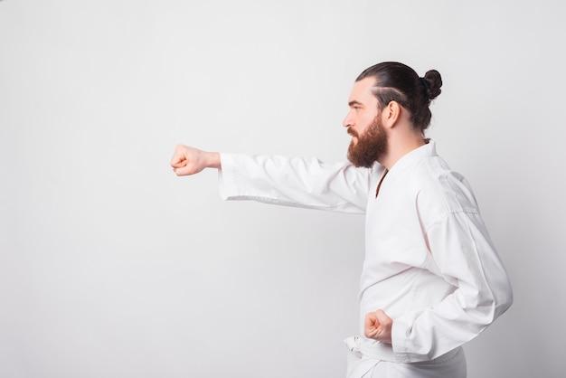 Zijaanzicht van een bebaarde man met taekwondo uniform ponsen over witte muur