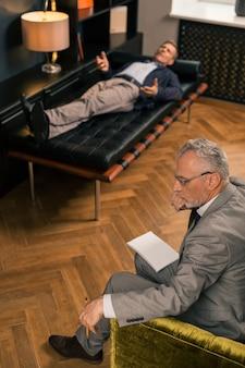 Zijaanzicht van een bedachtzame serieuze psychotherapeut die naast zijn patiënt zit terwijl hij een potlood in zijn hand houdt