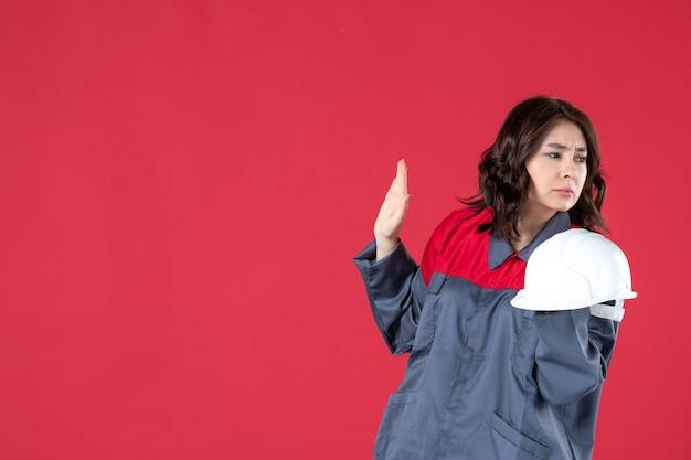 Zijaanzicht van een bezorgde vrouwelijke architect die een helm vasthoudt en op een geïsoleerde rode achtergrond staat