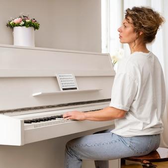Zijaanzicht van een blonde vrouw die de piano speelt