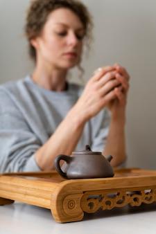 Zijaanzicht van een blonde vrouw met krullen die thee drinken en ontspannen