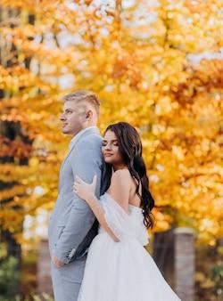 Zijaanzicht van een brunette bruid die haar bruidegom van achteren knuffelt in het herfstpark