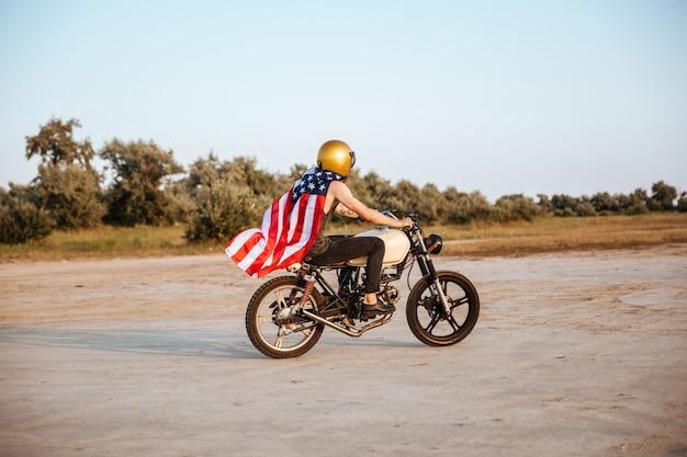 Zijaanzicht van een brute jongeman in gouden helm en amerikaanse vlagkaap retro motorfiets rijden