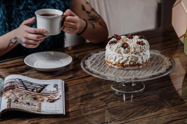 Zijaanzicht van een cake met slagroom en bessen op een glazen standaard en een persoon het drinken van thee aan de tafel