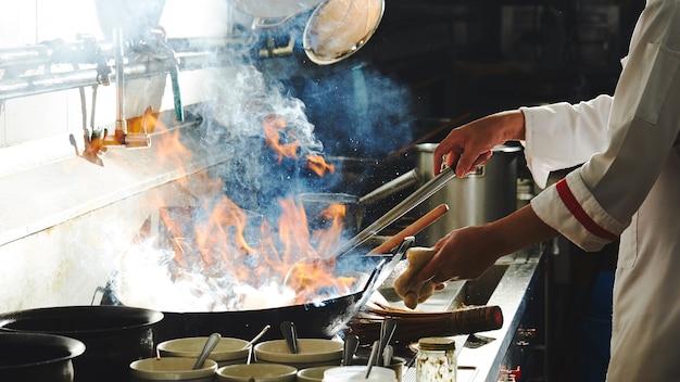 Zijaanzicht van een chef-kok die in de keuken kookt