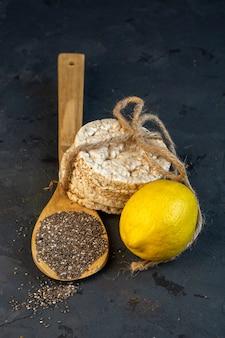 Zijaanzicht van een citroen met een houten lepel van zwarte zaden en rijstbroden gebonden met touw op zwart