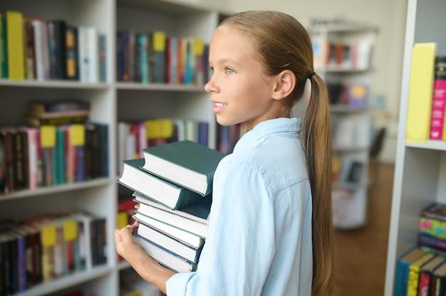 Zijaanzicht van een dromerig jong meisje met een stapel schoolboeken in haar handen die bij de bibliotheek staan